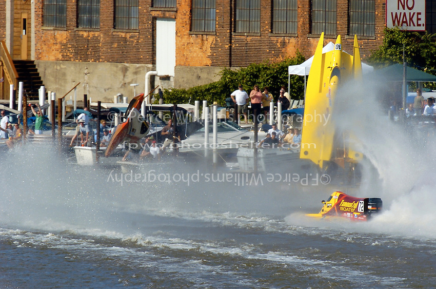 2004 Bay City River Roar, Bay City, Michigan, 26-27 June, 2004..Frame 4: Rinker strikes piling..Chris Fairchild (L, #62) and Terry Rinker (R,#10) come together during the inverted start for Saturday's 2 heat race. Both boats suffer a blowover, Fairchild's boat landing upside down in the river only to be run over by Todd Bowden. During Rinkers crash, his boat snagged a pier with the lower unit, ripping it away. The boat continued skyward, hitting the staircase from the lower to the upper pier and then striking a piling with the right rear of the hull, with that large chunk falling to the pier below (to be seen in a later picture. Rinker continued his backflip, finally landing just a few feet from a docked pleasure boat filled with spectators. No one was injured in the accident and both drivers made the restart in their backup boats...©F. Peirce Williams 2004..F. Peirce Williams .photography.P.O. Box 455 Eaton, Ohio 45320 USA.p: 317.358.7326 e: fpwp@mac.com