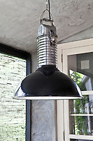 Close up of an industrial pendant light which hangs above the table in the kitchen/dining area