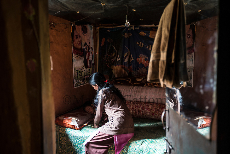 """Nepal - Kathmandu - Sunita Lama, 24 puts to sleep her 3 year old son Suren Lama. Sunita's husband, Sir Kumar Lama, 30, has just come back from Qatar, where he spent one year working as a welder in a factory. Rather than the promised around 360 USD per month, Lama was paid only 220 USD. Lama decided to come back to Nepal one year prior of the termination of its contract but is now struggling to repay the 1,200-USD-loan he had taken with his brother in order to go to Qatar. """"Most of my co-workers had been cheated as well"""" he explains. """"Some have been working for eight years now, but are still stuck in Qatar because of their debts""""."""