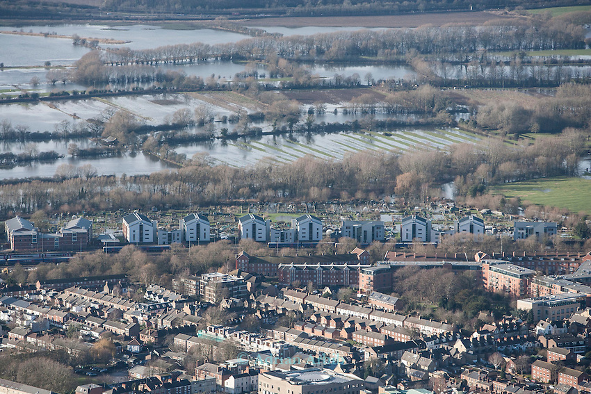 The  Thames, Oxford in  flood . <br /> View over Oxford  west  towards Binsey  and the southern edge of  Portmeadow, a natural flood plain. <br /> The controversial University buildings of Roger Dudman Way  can  be seen ( centre) along railway lines.