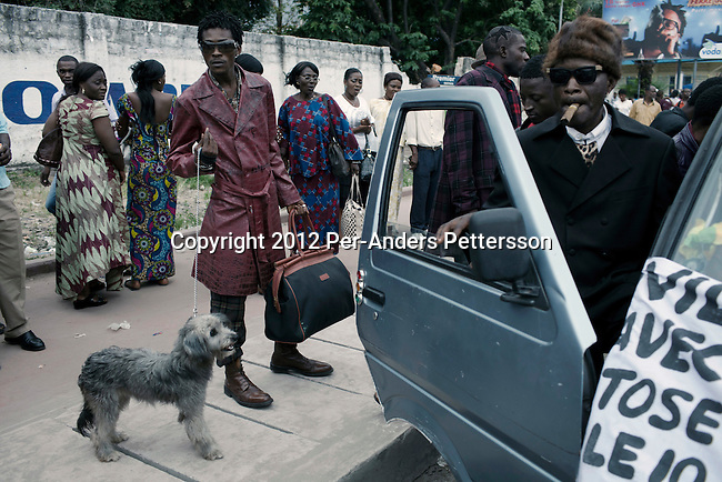 "KINSHASA, DEMOCRATIC REPUBLIC OF CONGO - FEBRUARY 10: Senior Sapeurs shows his designer label clothes and shoes on a busy street while paying their respect to Stervos Nyarcos, the founder of the .kitendi religion., which means clothing in local language Lingala. Nyarcos was known as the leader of the Sape movement, at Gombe cemetery on February 10, 2012 in Kinshasa, DRC. The word Sapeur comes from SAPE, a French acronym for Société des Ambianceurs et Persons Élégants. or .Society of Revellers and Elegant People. and it also means, .to dress with elegance and style"". Most of the young Sapeurs are unemployed, poor and live in harsh conditions in Kinshasa,  a city of about 10 million people. For many of them being a Sapeur means they can escape their daily struggles and dress like fashionable Europeans. Many hustle to build up their expensive collections. Most Sapeurs could never afford to visit Paris, and usually relatives send or bring clothes back to Kinshasa. (Photo by Per-Anders Pettersson)"