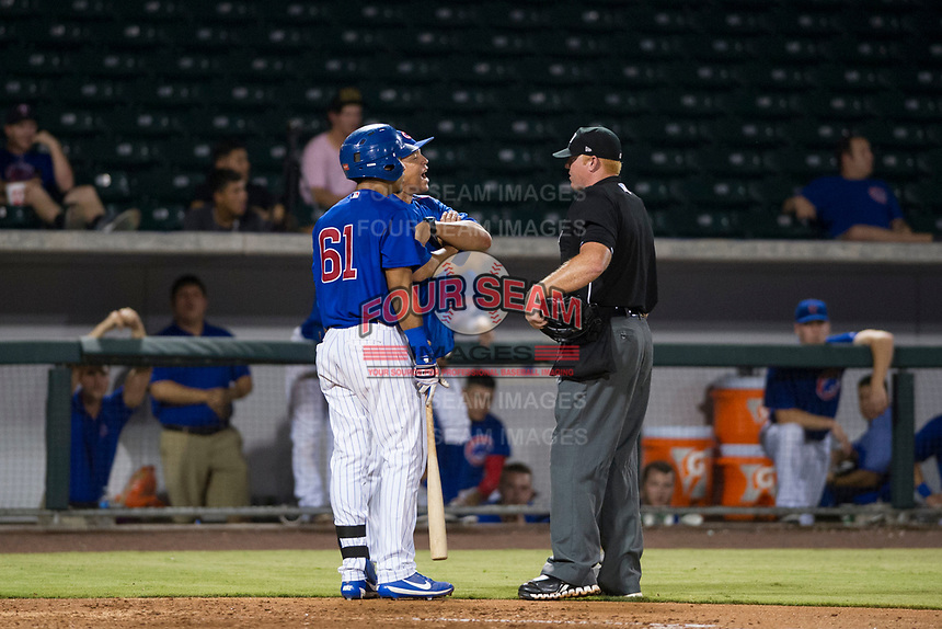 AZL Cubs designated hitter Yovanny Cuevas (61) and manager Carmelo Martinez argue with home plate umpire Ray Patchen after being called out for batter interference against the AZL Giants on September 6, 2017 at Sloan Park in Mesa, Arizona. AZL Giants defeated the AZL Cubs 6-5 to even up the Arizona League Championship Series at one game a piece. (Zachary Lucy/Four Seam Images)