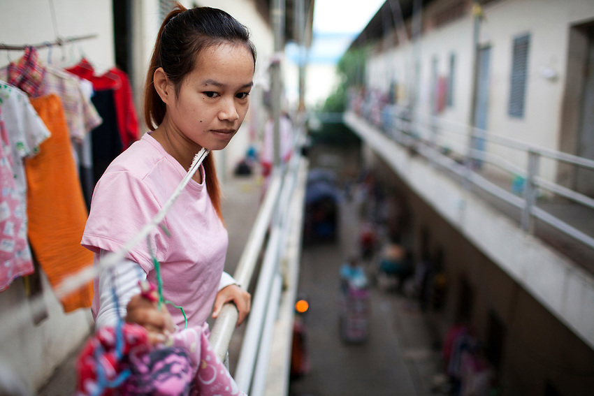 Keth Sreyroth, a 22-year-old worker at the Shen Zhou garment factory, looks down from the second floor where she lives in a room with 7 other factory workers, in a housing district near the Vattanac Industrial Park, in Phnom Penh, Cambodia, on September 15, 2011.