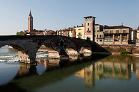 General view of Il Ponte Pietra, 100 BC, reflecting in the Adige River, Verona, Italy, with its Torre di Guardia (watch tower) and the bell tower of Basilica of  Saint Anastasia, 1280-1400, in the distance (on the left). The Via Postumia from Genua to the Brenner Pass crossed the Roman Ponte Pietra, or 'Stone Bridge', once known as the Pons Marmoreus. Its right hand arch was rebuilt in 1298 by Alberto I della Scala, and during the 2nd World War retreating German troops blew up 4 arches of the bridge,  which were rebuilt using original materials in 1957. Picture by Manuel Cohen.