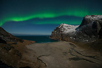 Northern lights shine in sky over Bunes beach, Moskenesøy, Lofoten Islands, Norway