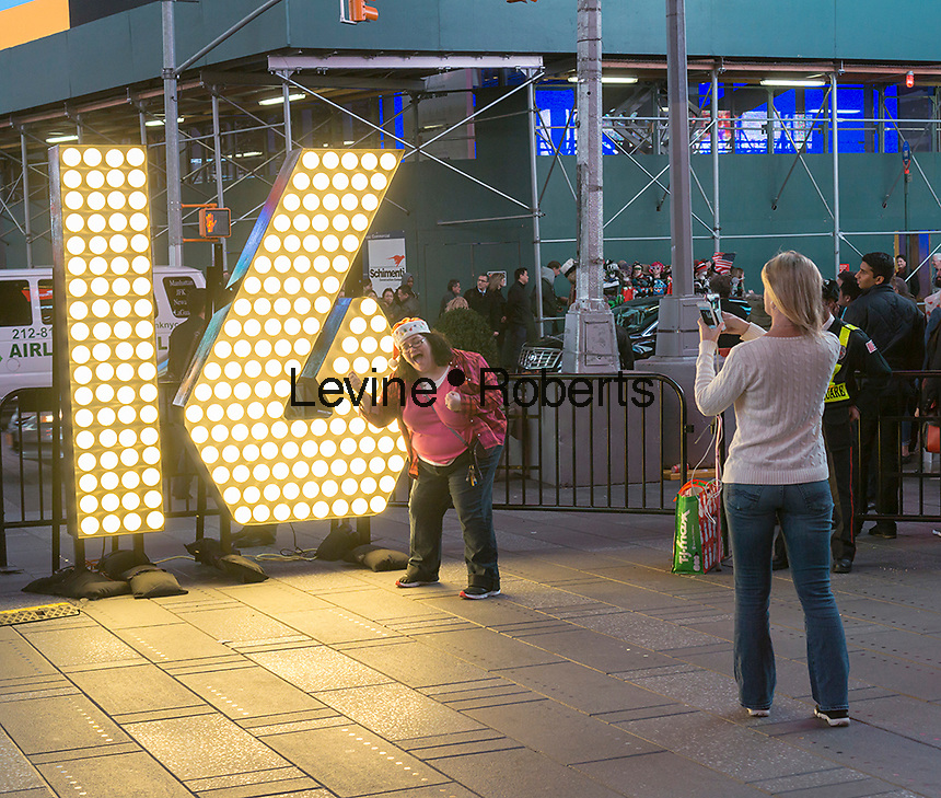 "Visitors to Times Square in New York pose in front of the two seven-foot-tall numerals ""1"" and ""6"" on Tuesday, December 15, 2015 .  The ""16"" will be part of the led display atop One Times Square which will light up at midnight January 1 spelling out ""2016"". The numbers use energy efficient LED bulbs which will last the entire year, never having to be changed.  (© Richard B. Levine)"