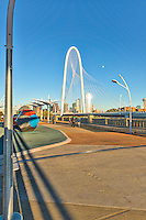 Dallas pedestrain bridge late afternoon with moon over the Margaret Hunt Hill Bridge and the city skyline in the background.