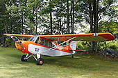 An orange and white, single engine, Aeronca 11AC Chief stands alone, with its wings appearing to be spread, on grass in front of the woods surrounding the airstrip of the 2010 Wings 'n' Wheels Showcase.