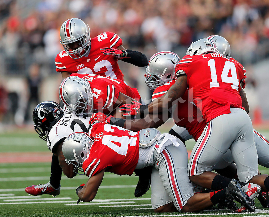 The Ohio State defense brings down Cincinnati Bearcats running back Hosey Williams (23) during the first quarter of Saturday's NCAA Division I football game at Ohio Stadium in Columbus on September 27, 2014. (Columbus Dispatch photo by Jonathan Quilter)