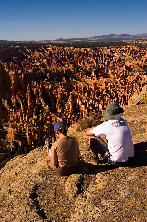 Couple relaxing at Bryce Canyon National Park, Ampitheater and Hoodoos of Silent City from Bryce Point, dawn, erosion, arid, Utah, UT, Southwest America, American Southwest, US, United States, tourists, travelers, sightseeing, no model release, Image ut344-18183, Photo copyright: Lee Foster, www.fostertravel.com, lee@fostertravel.com, 510-549-2202