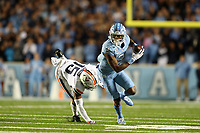 CHAPEL HILL, NC - NOVEMBER 02: Dyami Brown #2 of the University of North Carolina breaks a tackle attempt by De'Vante Cross #15 of the University of Virginia on his way to scoring his first touchdown during a game between University of Virginia and University of North Carolina at Kenan Memorial Stadium on November 02, 2019 in Chapel Hill, North Carolina.
