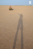 Girl riding an ATV in desert, Man's shade on sand (Licence this image exclusively with Getty: http://www.gettyimages.com/detail/110111193 )