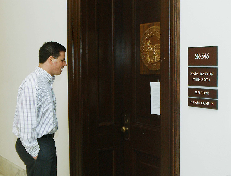 10/08/04.DAYTON CLOSES OFFICE IN RUSSELL BUILDING--Eli Greif, an aide for Sen. John Ensign, R-Nev., reads a statement by Sen. Mark Dayton, D-Minn., on the latter's office door regarding Dayton's closure of his Russell Building office on Tuesday. Dayton said information in a classified intelligence report had convinced him to keep his staff away from Capitol Hill until after the Nov. 2 election. .CONGRESSIONAL QUARTERLY PHOTO BY SCOTT J. FERRELL