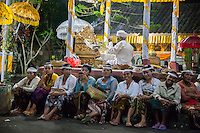 Bali, Indonesia.  While Hindu Priest Recites Prayers Women Wait for a Ceremony to Begin.  Pura Dalem Temple, Dlod Blungbang Village.
