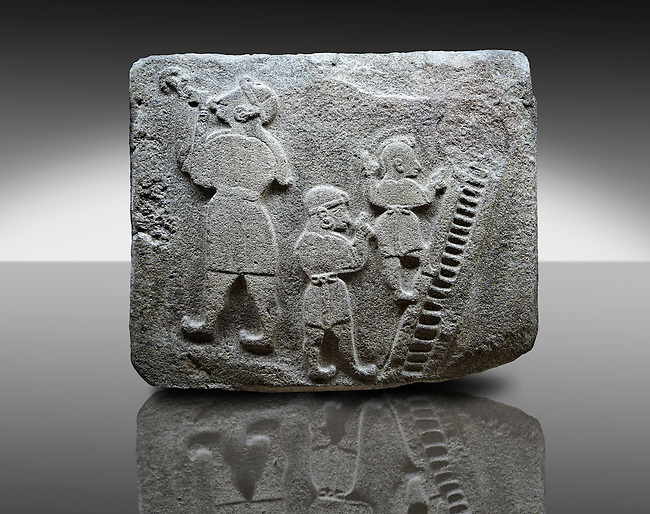 Picture & image of a Neo-Hittite orthostat showing a Conjurer & acrobats from Alacahöyük, Alaca Çorum Province, Turkey.  The conjurer on the left has long hair and is swallowing a dagger whilst the acrobats go up the stairs without holding on. All the figures are wearing horned headress and large looped earings. The acrobats are thought to be foreigners which is why they are smaller than the conjurer. Old Bronze age Chalcolithic Period. An Ankara Museum of Anatolian Civilizations exhibit.