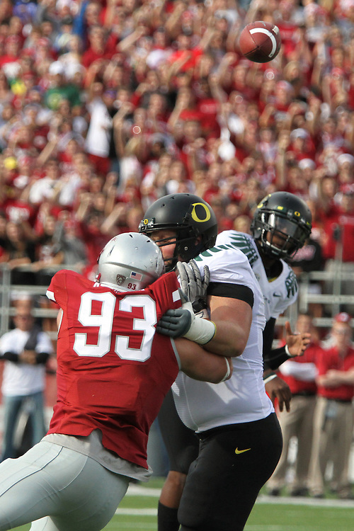 Oregon quarterback, Darron Thomas, fires a pass over defensive pressure from Washington State's Kevin Kooyman (#93) during the Ducks Pac-10 conference game against the Cougars at Martin Stadium in Pullman, Washington, on October 9, 2010.  In a game that went back and forth early in to the fourth quarter, Oregon finally prevailed over the Cougars, 43-23.