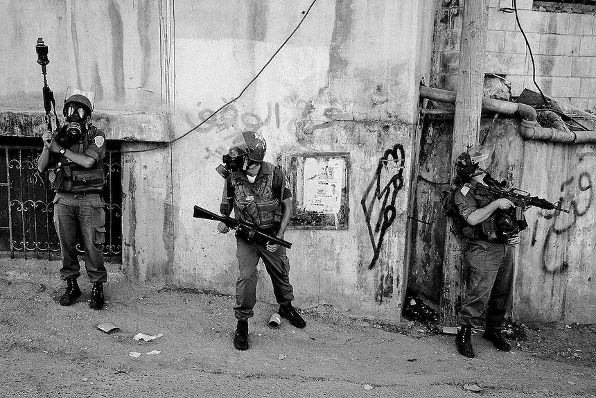 Israeli soldiers take cover during clashes with Palestinian youths at the Qalandiya checkpoint, The West Bank, October 2009. Photo: Ed Giles.