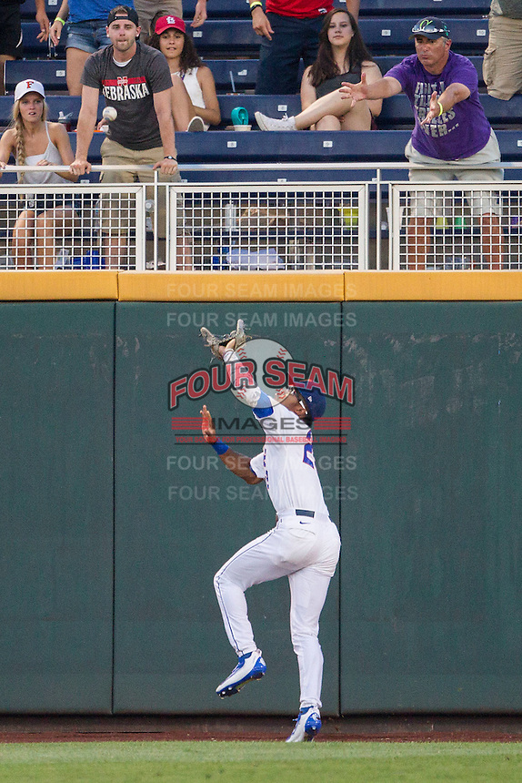 Florida Gators outfielder Buddy Reed (23) attempts to make a catch against the wall against the Coastal Carolina Chanticleers in Game 4 of the NCAA College World Series on June 19, 2016 at TD Ameritrade Park in Omaha, Nebraska. Coastal Carolina defeated Florida 2-1. (Andrew Woolley/Four Seam Images)