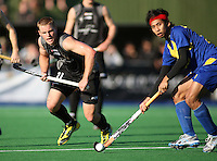 Malaysia's Hafifi Hafiz Hanafin looks to pass under pressure from Steve Edwards during the international hockey match between the New Zealand Black Sticks and Malaysia at Fitzherbert Park, Palmerston North, New Zealand on Sunday, 9 August 2009. Photo: Dave Lintott / lintottphoto.co.nz