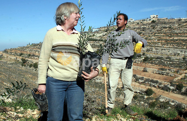 Israeli and foreign peace activists help Palestinian farmers to cultivate their land during a demonstration on farming land near the Jewish settlement of Karmi Tsor, north of the occupied flashpoint West Bank city of Hebron, 10 February 2010. Israeli troops dispersed the protesters who were demanding the right of Palestinian farmers to cultivate their land near the settlement, following a ban for security reasons. Photo by Najeh Hashlamoun