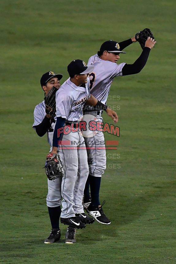 Outfielders Carlos Vidal (2), Dom Thompson-Williams (15) and Isiah Gilliam (25) of the Charleston RiverDogs body bump after Game 2 of the South Atlantic League Southern Division Playoff against the Greenville Drive on Friday, September 8, 2017, at Fluor Field at the West End in Greenville, South Carolina. Charleston won, 2-1, and the series is tied at one game each. (Tom Priddy/Four Seam Images)