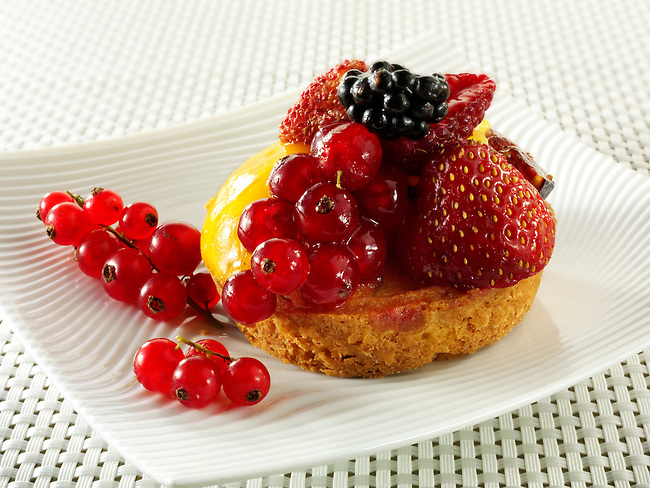 A modern fruit cake with redcurrants, wild strawberries, blacberry and creme patisserie in a light sponge case in a designer dish.