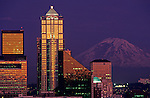 Seattle skyline illuminated at dusk with city lights office buildings and Mount Rainier Seattle Washington USA