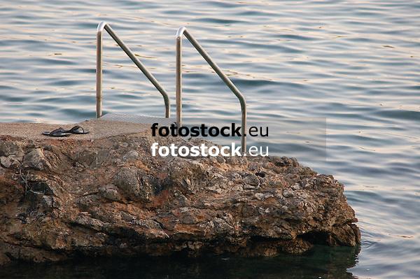 shoes beside ladder at rocky coast<br /> <br /> zapatos al lado de una escalera en costa rocosa<br /> <br /> Schuhe neben einer Badeleiter an felsiger K&uuml;ste<br /> <br /> 3008 x 2000 px<br /> 150 dpi: 50,94 x 33,87 cm<br /> 300 dpi: 25,47 x 16,93 cm