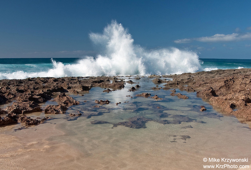 A wave breaks on the rocky shoreline of Keiki Beach, North Shore, Oahu