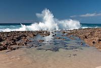 A wave breaks on the rocky shoreline of Keiki Beach, North Shore, Oahu