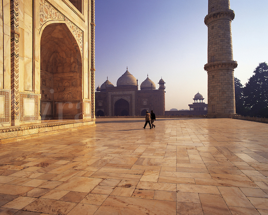 Two tourists are dwarfed by the massive scale of the upper tiled area of the Taj Mahal, Agra, Indi