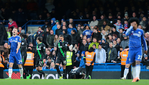 05.03.2016. Stamford Bridge, London, England. Barclays Premier League. Chelsea versus Stoke City. Stoke City Forward Mame Biram Diouf kisses the grass after scoring a rebound header past Chelsea Goalkeeper Thibaut Courtois (left) to level the score at 1-1. Chelsea  Willian and Gary Cahill react to a late goal