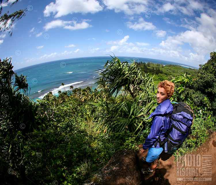 A young local woman with a backpack pauses on Kalalalu Trail, overlooking Ke'e Beach, Na Pali Coast, Kaua'i.