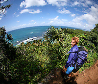A young local woman with a backpack pauses on Kalalalu Trail, overlooking Ke'e Beach, Na Pali Coast, Kaua'i.