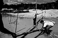 Health agent travel all over Amazon gold mining areas in order to collect blood from possibly malaria-infected gold seekers. Malaria, a mosquito-borne infectious disease is endemic in this region near Agua Branca gold mining village in Para State, Brazil. The disease results from the multiplication of malaria parasites within red blood cells, causing symptoms that typically include fever and headache, in severe cases progressing to coma, and death. Malaria transmission can be reduced by preventing mosquito bites by distribution of inexpensive mosquito nets and insect repellents, or by mosquito-control measures such as spraying insecticides inside houses or by pulverizing it in the village streets and draining standing water where mosquitoes lay their eggs.