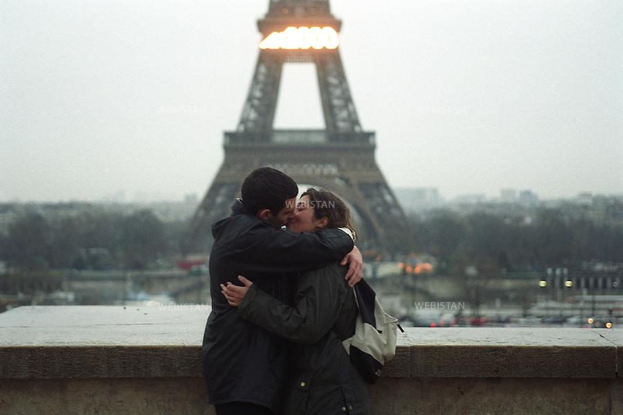 A couple kiss in front of the Eiffel Tower. Un couple s'embrasse devant la Tour Eiffel.