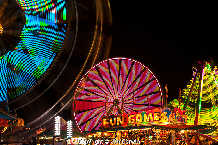 Evergreen State Fair with ferris wheel and game booths at night