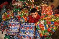 Boy surrounded by lots of presents on Christmas day