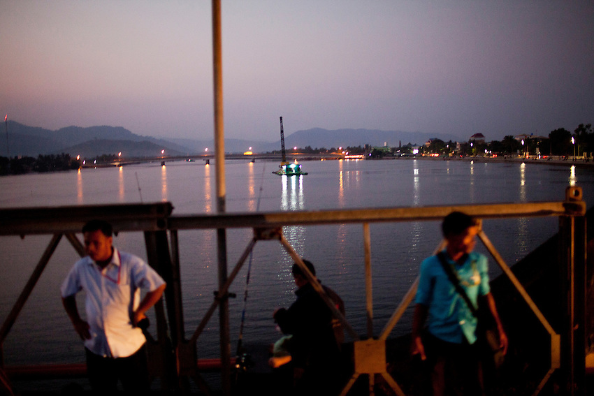 Men stand on a bridge across the Kampong bay river at night in Kampot province, Cambodia, February 10, 2012. In the background, a sand dredging crane can be seen.