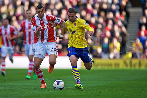 01.03.2014  Stoke, England. Stoke City FC defender Geoff Cameron and Arsenal forward Lukas Podolski in action during the Barclays Premier League game between Stoke City and Arsenal from The Britannia Stadium.