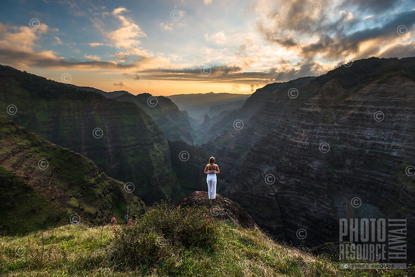 At sunset, a woman holds a yoga pose in a remote canyon in Koke'e State Park on Kaua'i.