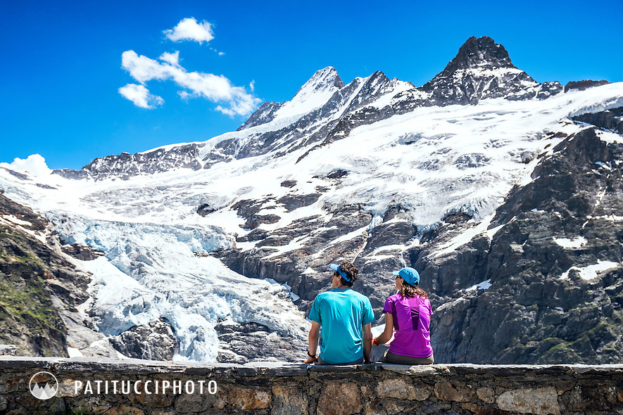 A couple sits on a wall outside the Gleckstein Hut, above Grindelwald, Switzerland, looking at views of the surrounding glaciers and the 4000 meter Schreckhorn