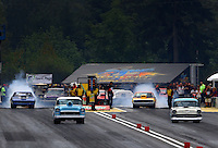 Aug. 3, 2013; Kent, WA, USA: NHRA super street drivers race down track as the pair behind do their burnouts during qualifying for the Northwest Nationals at Pacific Raceways. Mandatory Credit: Mark J. Rebilas-USA TODAY Sports