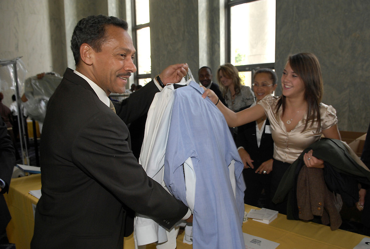 "Mel Watt, D-NC, makes a donation to Lanea Warren at the Working Wardrobes, Men's Wearhouse, and the American League of Lobbyists annual ""Capitol PurSuit Drive"" to collect business attire from Congress to aid low-income adults seeking to re-enter the workforce. The event was held in the Rayburn House Office Building foyer.."