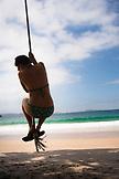 NEW ZEALAND, Coromandel Peninsula, Woman on Rope Swing on Hahei Beach, Ben M Thomas