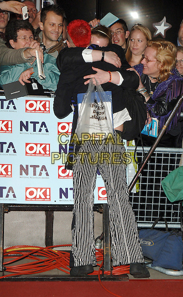 PETE BENNETT - BIG BROTHER.The National Television Awards 2006, Royal Albert Hall, London, UK. .October 31st, 2006.full length back behind rear black white striped stripes trousers hug embrace audience crowd fans gesture.CAP/BEL.©Belcher/Capital Pictures