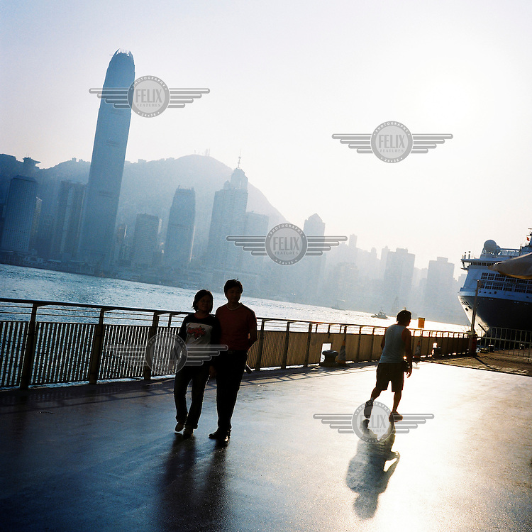 People walk on the riverside in Hong Kong.