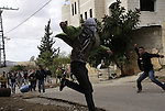 Palestinian protesters throw stones towards Israeli soldiers during clashes that broke out at a weekly demonstration against Israeli-occupation in the northern West Bank village of Kfar Kadum on December 9, 2011. A Palestinian was critically wounded when he was hit in the face by a tear gas canister fired by Israeli troops at a rally in Nabi Saleh, some 10 kilometres (six miles) northwest of Ramallah, medics and witnesses said. Photo by Wagdi Eshtayah.