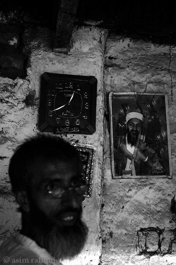 a photograph of osama bin laden decorates a wall in a gun factory.  darra adam khel, tribal areas, pakistan.  september 2003&amp;#xA;&amp;#xA;copyright asim rafiqui 2003<br />