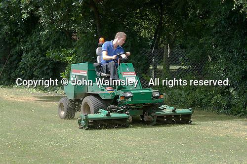 Groundsman cutting the grass,  State Secondary Roman Catholic school.